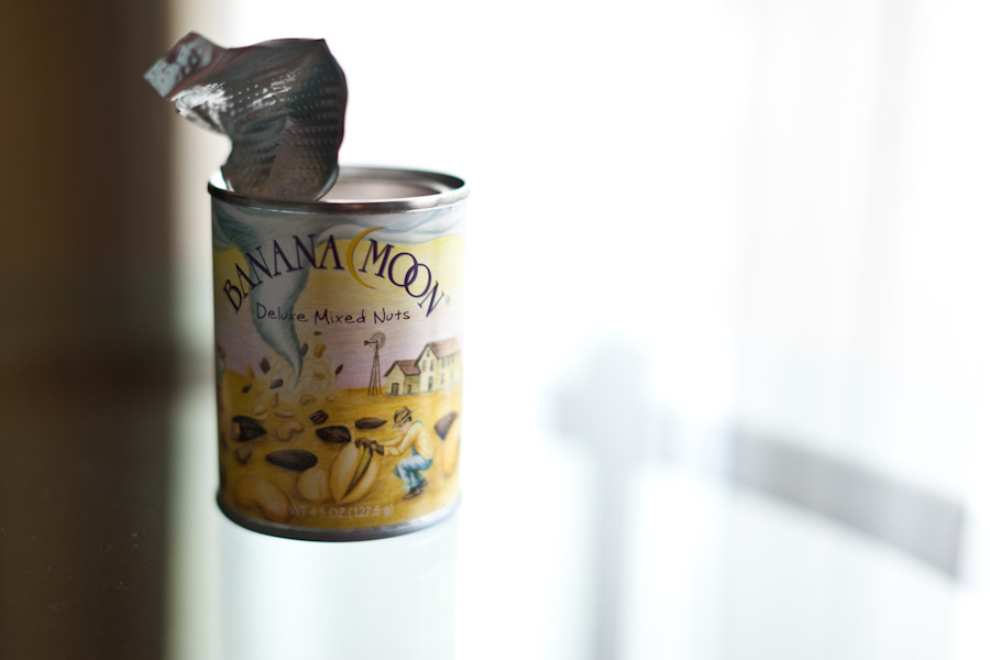 open can of mixed nuts floating on glass table