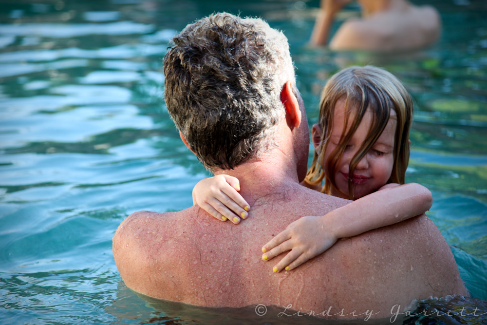 girl-in-daddys-arms-in-pool
