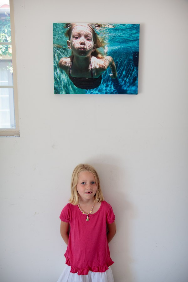 girl standing under photo of her